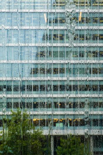 Building seen through wet window during rainy season