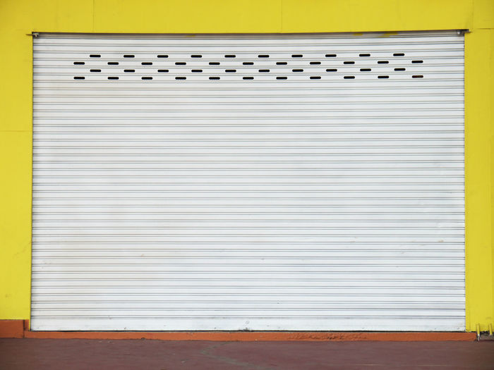 Closed shutter of yellow wall