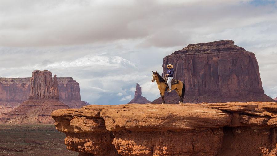 Full length of man sitting on horse over rocky cliff against sky