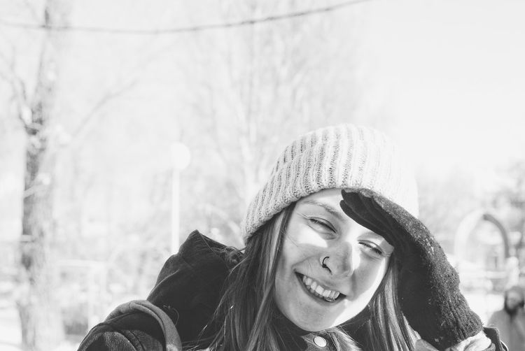 Smiling young woman covering eyes from sunlight during winter