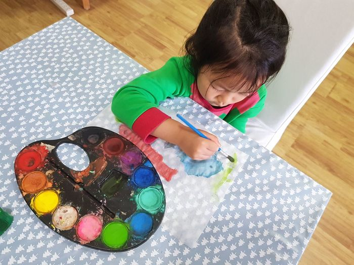 High angle view of girl painting on table