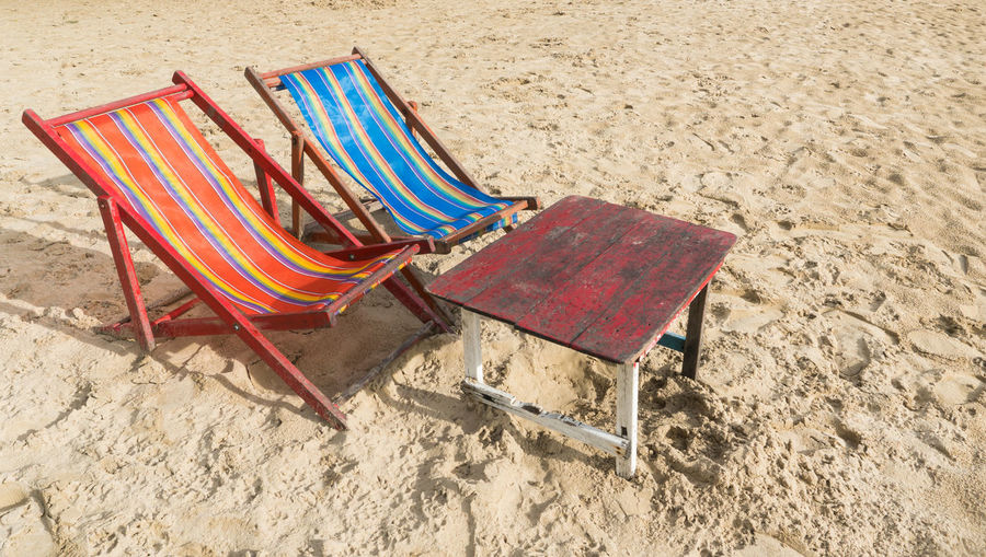 High angle view of chairs on sand at beach