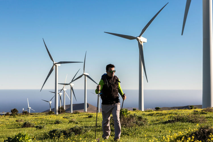 Full length of man walking against wind turbines