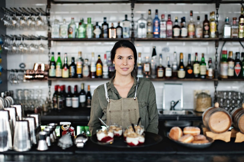 Portrait of woman standing by display at market stall