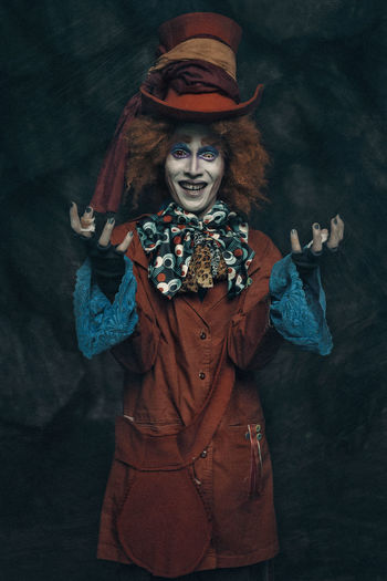 Portrait of man wearing costume against black background