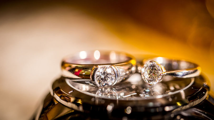 a couple of diamond ring on the watch for the engagement ceremony Couple Engagement Glitter Gold Wedding Close-up Diamond Ring Engagement Ring Gold Gold Colored Jewelry Luxury No People Platinum Ring Watch