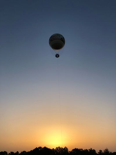 Low Angle View Of Hot Air Balloon Flying Against Sky During Sunset
