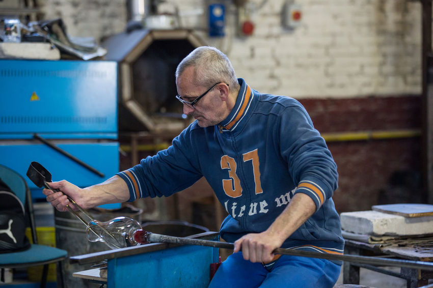 Adult Day Factory Glass - Material Glass Factory Indoors  Manual Worker Manufacturing Occupation Mature Adult Men Metal Industry Muranoglass Occupation One Person People Protective Workwear Real People Working Workshop