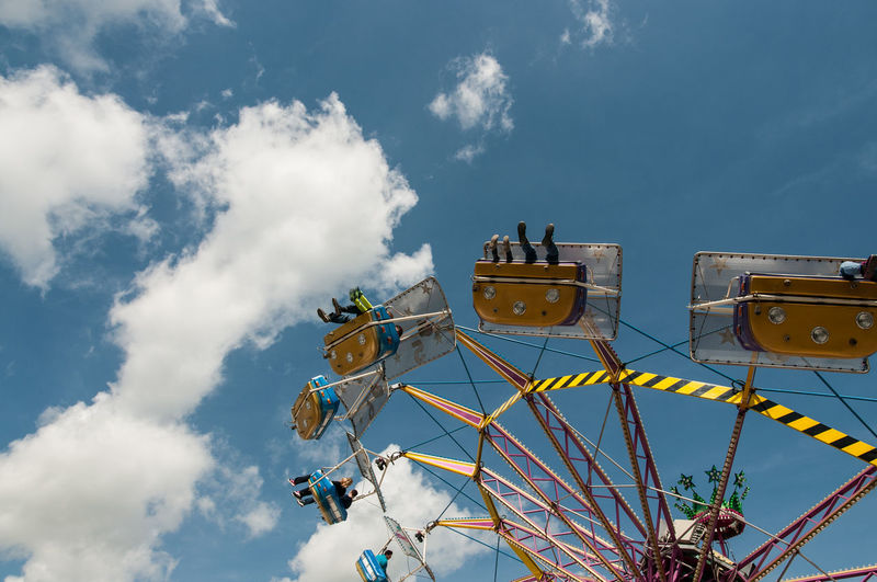 Low angle view of people enjoying merry-go-round against sky