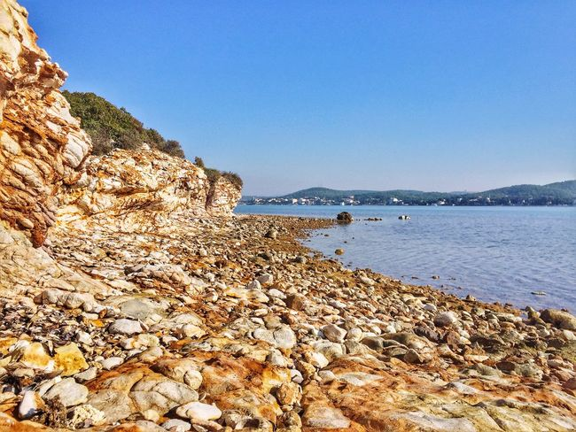 Beauty In Nature Scenics Tranquil Scene Outdoors Pebble Pebble Beach Natural Beauty Waterfront Nature Moments Beauty In Nature Clear Sky Water Nature Rock - Object Sea Beach Tranquility Day No People Sky Mountain
