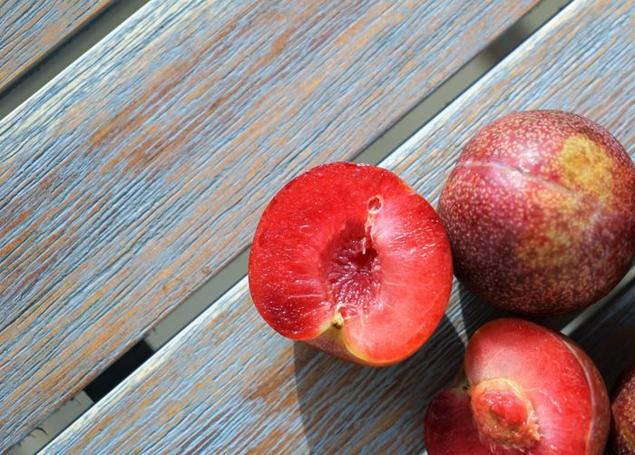 Close up view on red plums at wooden surface