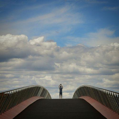 People walking on railing against cloudy sky