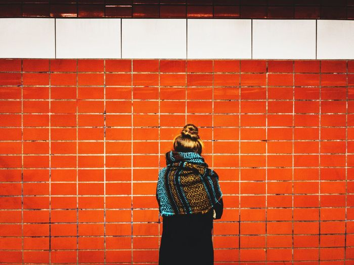 woman's back with scarf in front of orange background Beautiful Woman Young Woman Warm Clothing Underground Station  Train Station Subway Station Street Photography Urban Exploration Tiles Orange Background Orange Color Contemporary Scarf From Behind Behind Back Backside One Person Real People Orange Color Standing Red Day Outdoors Adult