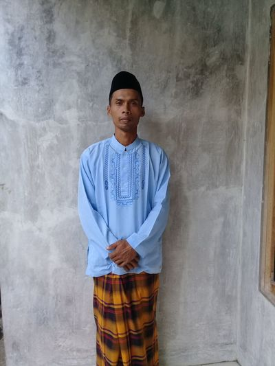 Portrait of man wearing traditional clothing while standing against wall