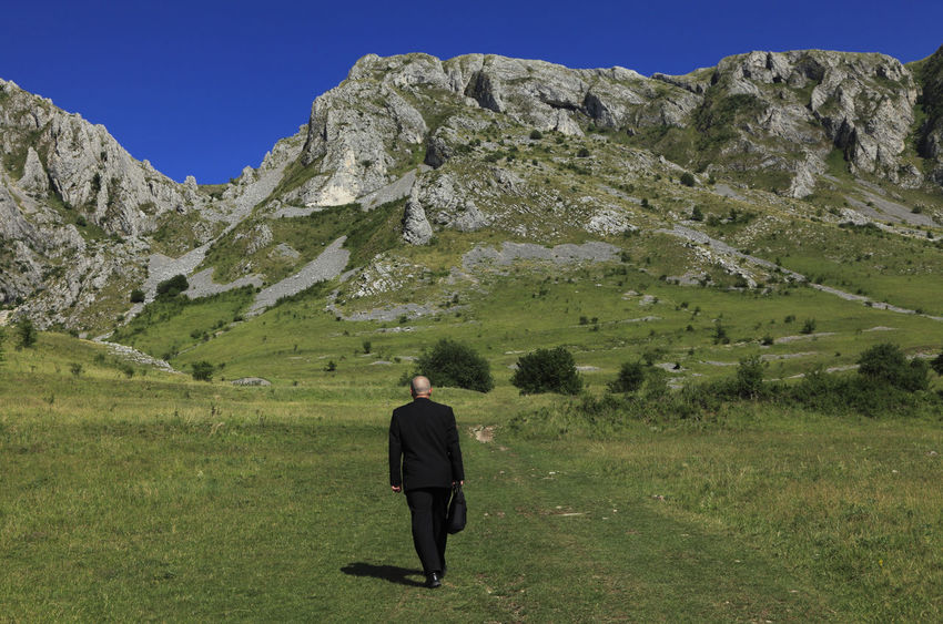 Businessman walking on grass near rocky mountains. Business Scenic Black Suit Businessman Concept Field Full Length Grass Green Color Landscape Leisure Activity Lifestyles Mountain Nature One Person Outdoors People Real People Rear View Scenics Strategy Walking Well-dressed Mobility In Mega Cities