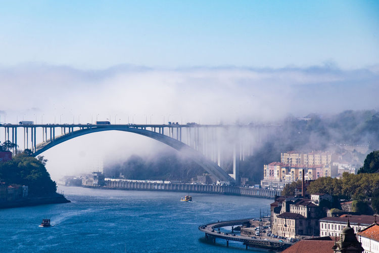 Bridge Over River In City During Foggy Weather