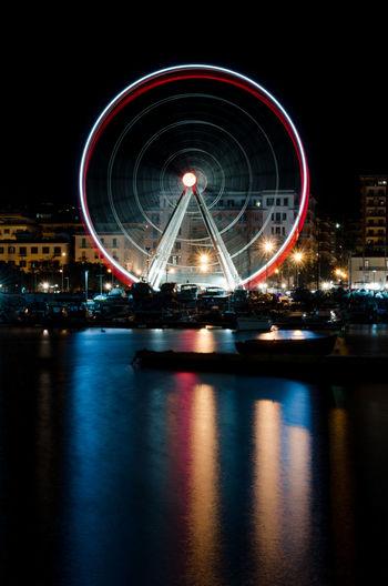 Illuminated ferris wheel by lake in city at night