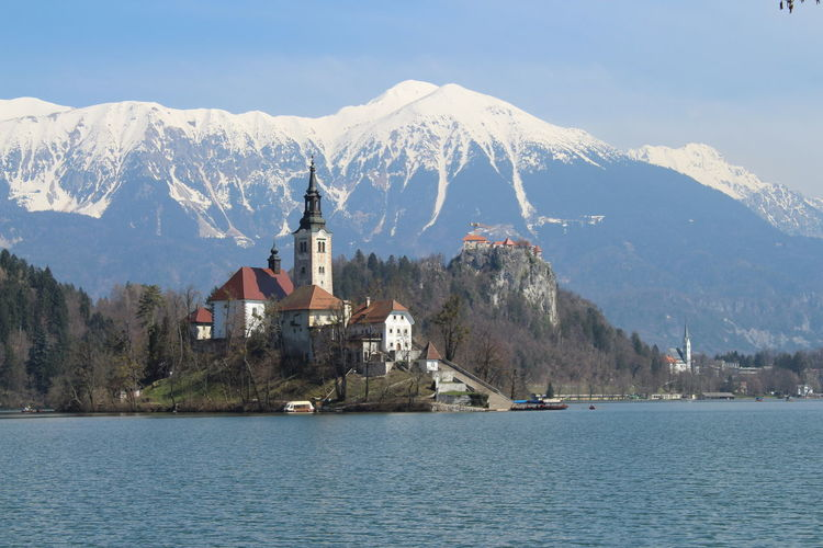 Church by lake against snowcapped mountain