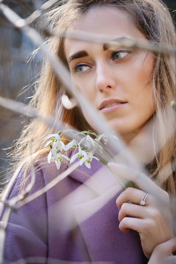 Portrait of a beautiful young woman holding red flowering plant