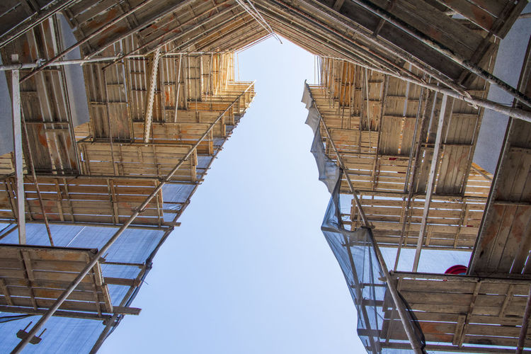 Low angle view of building under construction against clear sky