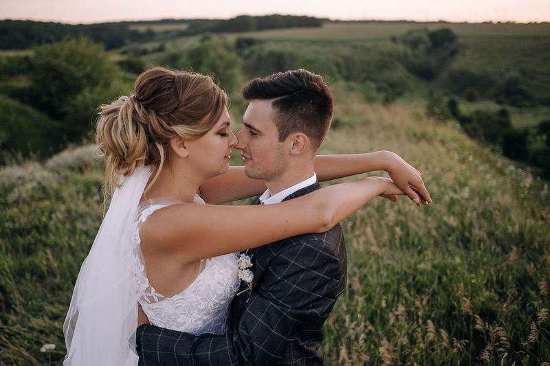 Side view of newlywed couple rubbing noses on grassy field
