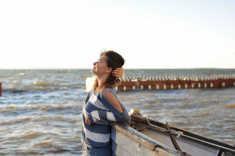 Brunette girl in striped sweater, bare shoulder and denim skirt, smiling near an old gray boat