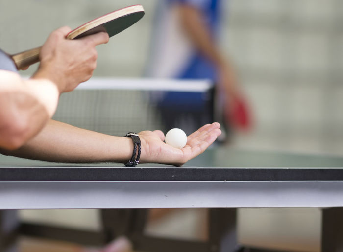 Cropped hands of man playing table tennis
