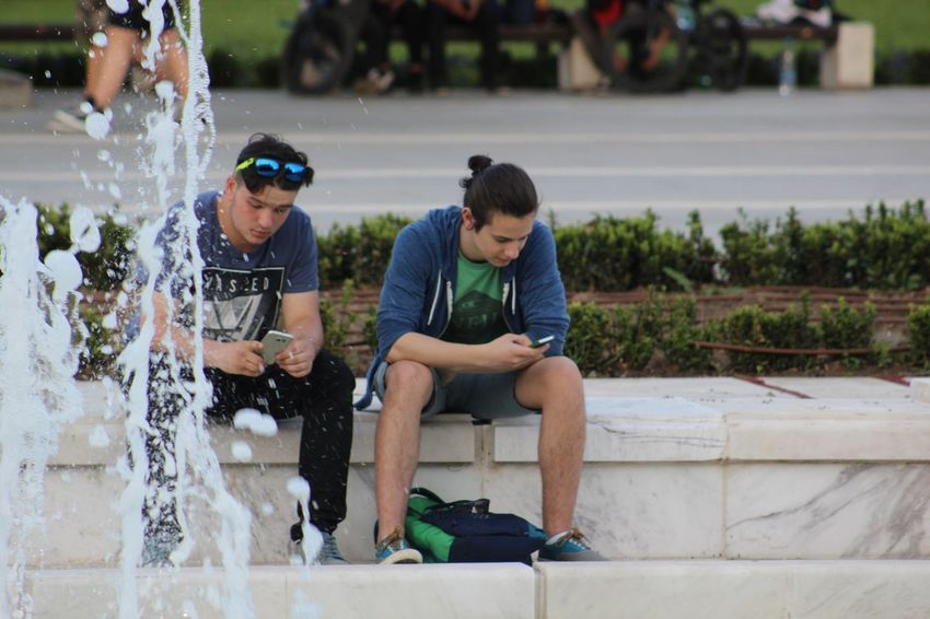Boys Casual Clothing Cute Day Enjoyment Focus On Foreground Fountain Fun Leisure Activity Lifestyles Outdoors Portrait Sitting Smartphone Street Photography Technology The Street Photographer - 2016 EyeEm Awards Urban Urban Landscape Water The Essence Of Summer
