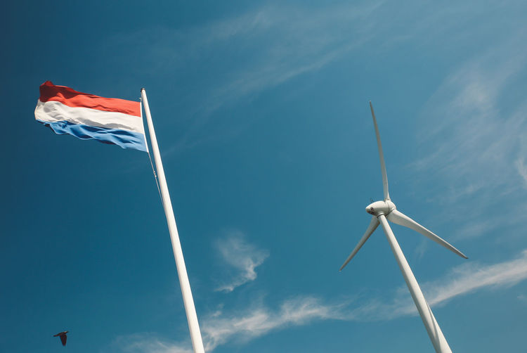 Low angle view of windmill and dutch flag against sky