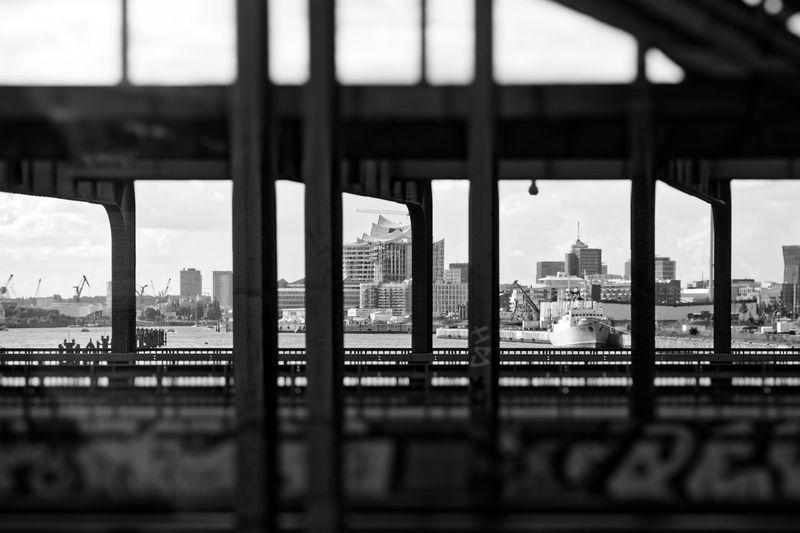 View of city buildings seen through bridge