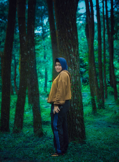 Full length side view of young woman standing by tree trunk in forest