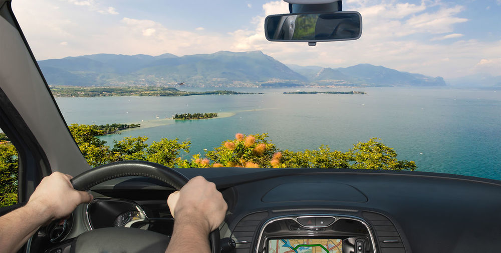 Cropped hands of man driving car against sea