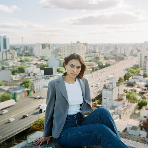Portrait of smiling young woman sitting against cityscape