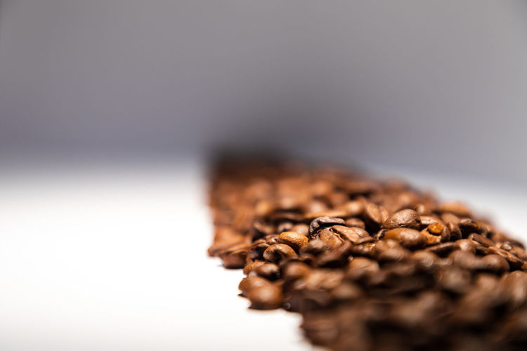 long line of fresh roasted coffee beans Antioxidant Brown Close-up Coffee Coffee - Drink Colored Background Copy Space Drink Extreme Close-up Food Food And Drink Freshness Healthy Eating Indoors  No People Roasted Coffee Bean Seed Selective Focus Still Life Studio Shot Wellbeing
