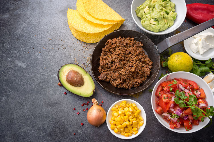 filling tacos with roasted beef, tomatoes, corn and guacamole, all ingredients on a dark stone background with copy space, top view from above Beef SPAIN Tacos Above View Avocado Day DIP Flat Lay Food Food And Drink Freshness Fried Ground Guacamole High Angle View Indoors  Lime Mexican Food No People Pan Tomato Variation
