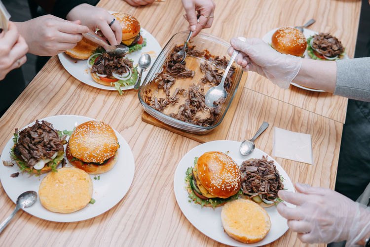 Burgers with beef and vegetables, the cooking process, hands collecting the burger.