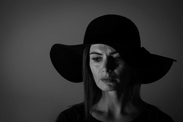 Close-up of woman wearing hat against gray background