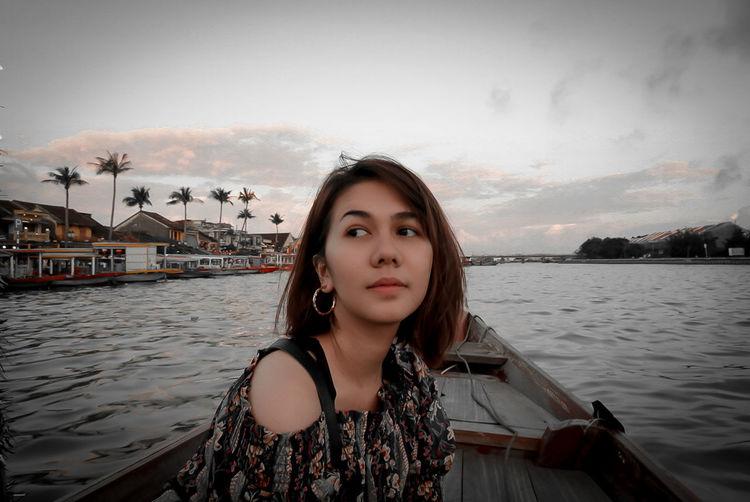 Portrait of beautiful woman in boat against sky