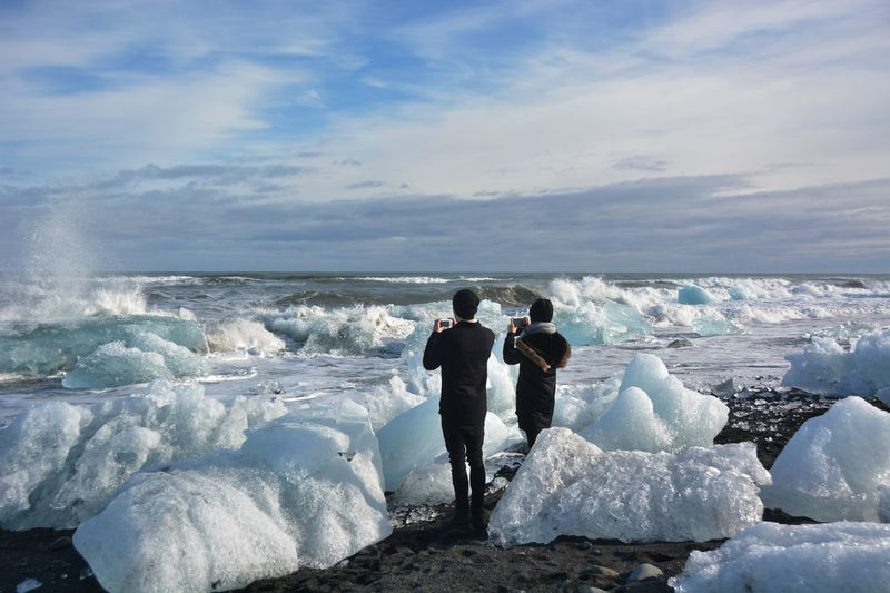 REAR VIEW OF PEOPLE TAKING PHOTOS OF ICE FORMATIONS IN SEA