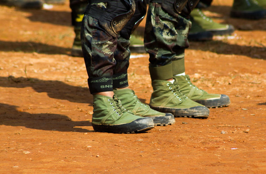 Unidentified A Soldier at Shan State in Myanmar EyeEmNewHere Armed Forces Army Soldier Body Part Camouflage Clothing Clothing Day Government Human Body Part Human Foot Human Leg Human Limb Low Section Military Nature Outdoors People Real People Shadow Shoe Standing Sunlight Uniform