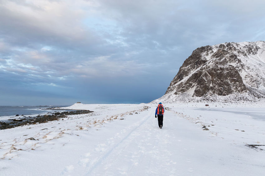 Man walking along a snowcapped seashore FootPrint Footpath Frozen Hiking Ice Norwegian Sea Adventure Arctic Backpack Beauty In Nature Cloud - Sky Cold Temperature Day Full Length Getting Away From It All Idyllic Lake Leisure Activity Lifestyles Lofoten And Vesteral Islands Mountain Nature One Man Only One Person Only Men Outdoors People Real People Rear View Remote Scenics Sea Sky Snow Track - Imprint Tranquil Scene Tranquility Walking Weather Winter