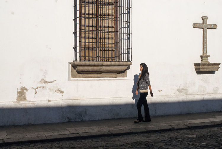 Young woman walking in the street Alone Beautiful Believer Catholic Colonial Architecture Creative Light And Shadow Cross Elegant Faith Going To Work Historic Historical Building INRI Jesus Latin America Morning Religion Serious Street Street Photography Sunlight Sunny Walking Window Young Women