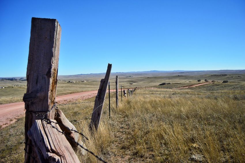 Along rural country road Wooden Post West Of Lusk Wyoming Fence Barbed Wire Outdoors Sunshine Gravel Road Clear Sky Sunny Blue Landscape Remote Countryside