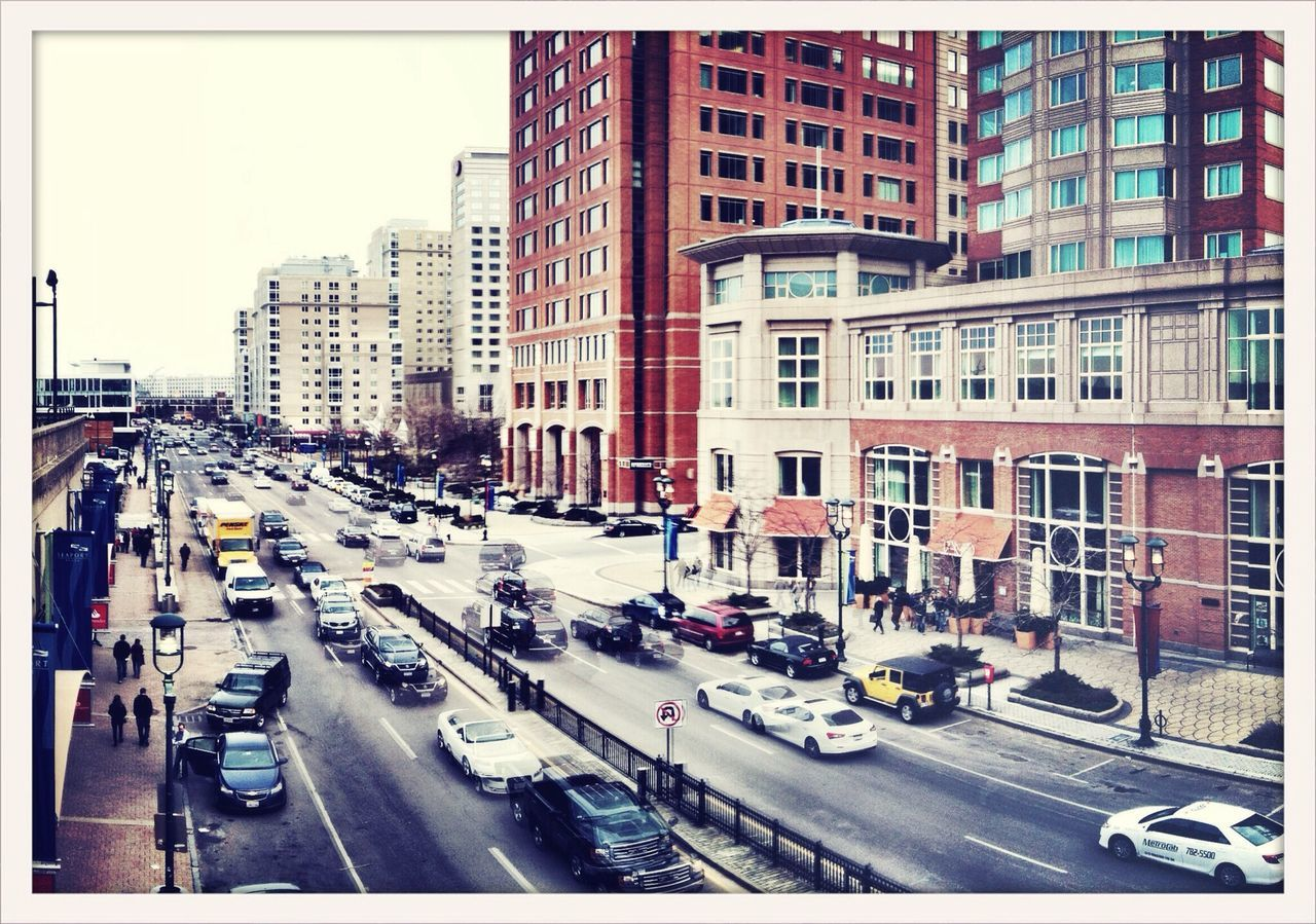 transportation, city, traffic, architecture, car, building exterior, street, land vehicle, built structure, road, city street, city life, mode of transport, outdoors, day, skyscraper, tall, cityscape, no people, sky