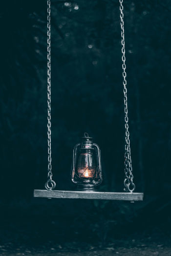 Close-up of illuminated lantern on swing