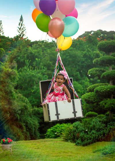 Portrait of cute girl in suitcase floating while tied to balloons
