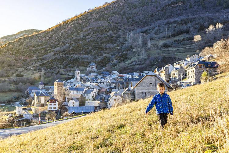Boy walking on field against mountains