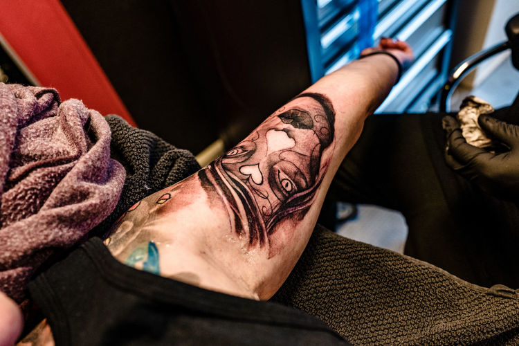 Close-up of artist tattooing design on human skin