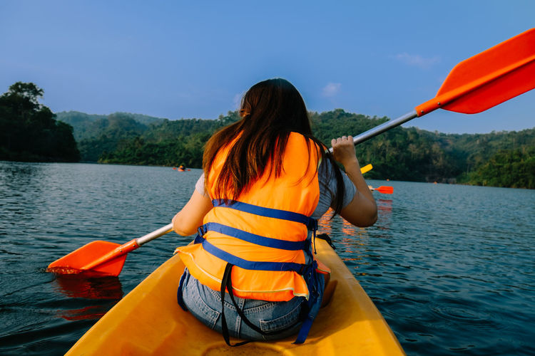 Adventure Beauty In Nature Casual Clothing Day Holding Kayak Lake Leisure Activity Life Jacket Lifestyles Nature Nautical Vessel Oar One Person Outdoors Real People Rear View Rowing Scenics Sitting Transportation Tree Vacations Water Women