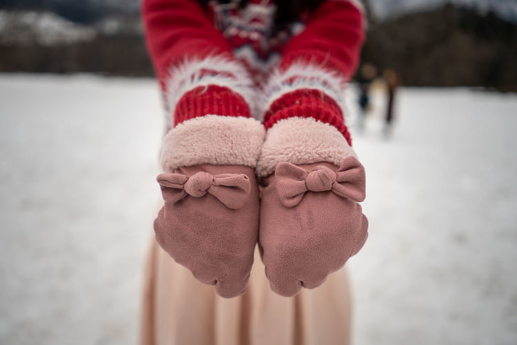 Midsection of woman showing gloves while standing on land during winter